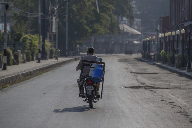 A Kashmiri milkman drives his motorcycle on a deserted street on the first anniversary of India's decision to revoke the disputed region's semi-autonomy, in Srinagar, Indian controlled Kashmir, Wednesday, August 5, 2020. Last year on Aug. 5, India's Hindu-nationalist-led government of Prime Minister Narendra Modi stripped Jammu-Kashmir of its statehood and divided it into two federally governed territories. Late Tuesday, authorities lifted a curfew in Srinagar but said restrictions on public movement, transport and commercial activities would continue because of the coronavirus pandemic. (Photo by Dar Yasin/AP Photo)