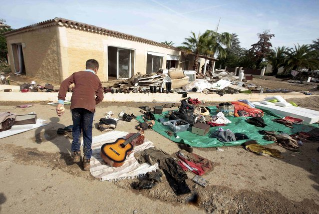 A boy walks past belongings put out to dry in front of his home after flooding caused by torrential rain in Biot, France, October 4, 2015. (Photo by Eric Gaillard/Reuters)