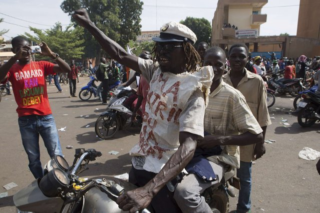 People celebrate the departure of Burkina Faso's President Blaise Compaore in Ouagadougou, capital of Burkina Faso, October 31, 2014. General Honore Traore, the head of Burkina Faso's armed forces, took power on Friday after Compaore resigned amid mass demonstrations against an attempt to extend his 27-year rule in the West African country. (Photo by Joe Penney/Reuters)