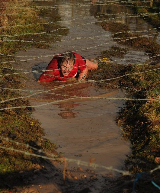 A competitor  crawls under barbed wire during the Tough Guy Challenge endurance race on January 27, 2013 in Telford, England. Every year thousands of people run the 8 mile assault course which involves freezing temperatures, fire and ice.  (Photo by Michael Regan)