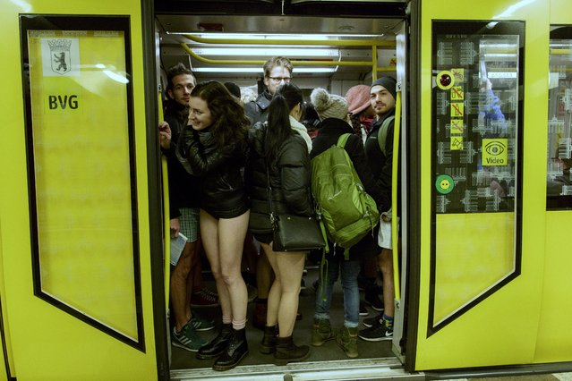Participants of the No Pants Subway Ride By Odlo ride a commuter train on January 7, 2018 in Berlin, Germany. The annual event, in which participants board a subway car in January while not wearing any pants, began as a joke by the public prank group Improv Everywhere in New York City. This year's No Pants Subway Ride was organized by the sportswear company Odlo. (Photo by Carsten Koall/Getty Images)
