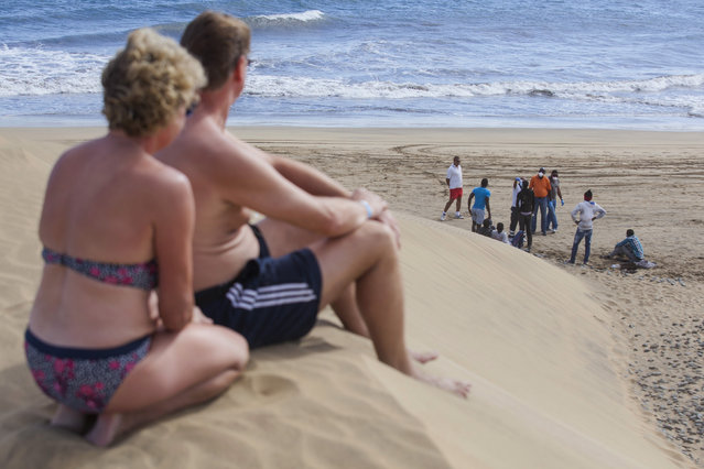 Tourists look at would-be immigrants at the Maspalomas beach, on Gran Canaria in Spain's Canary Islands, after some 21 would-be immigrants arrived in a fishing boat on their way to European soil from Africa, November 5, 2014. (Photo by Borja Suarez/Reuters)