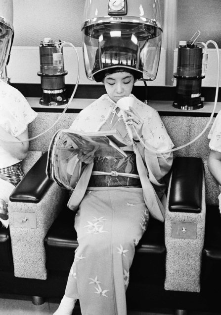 Japanese women inhale pure air from oxygen tanks at a Tokyo beauty shop while they sit under hair-driers, October 13, 1966, Tokyo, Japan. Several midget oxygen tanks are available so that customers can feel refreshed. The woman is unidentified. (Photo by AP Photo)