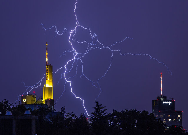 In this Tuesday, June 7, 2016 photo lightning is pictured between the bank buildings of Commerzbank, left, and the local Helaba bank in Frankfurt, central Germany. (Photo by Frank Rumpenhorst/DPA via AP Photo)