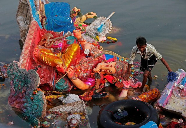 A man collects items thrown as offerings by worshippers into the Sabarmati river, a day after the immersion of idols of the Hindu god Ganesh, the deity of prosperity, in Ahmedabad, India September 16, 2016. (Photo by Amit Dave/Reuters)
