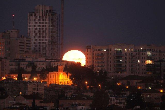 The moon sets behind the city of Jerusalem early on January  31, 2018. (Photo by Menahem Kahana/AFP Photo)