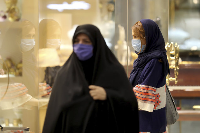 Women wearing protective face masks to help prevent spread of the coronavirus walk through a shopping center, in Tehran, Iran, Wednesday, August 19, 2020. Iran surpassed 20,000 confirmed deaths from the coronavirus on Wednesday, the health ministry said — the highest death toll for any Middle East country so far in the pandemic. (Photo by Ebrahim Noroozi/AP Photo)