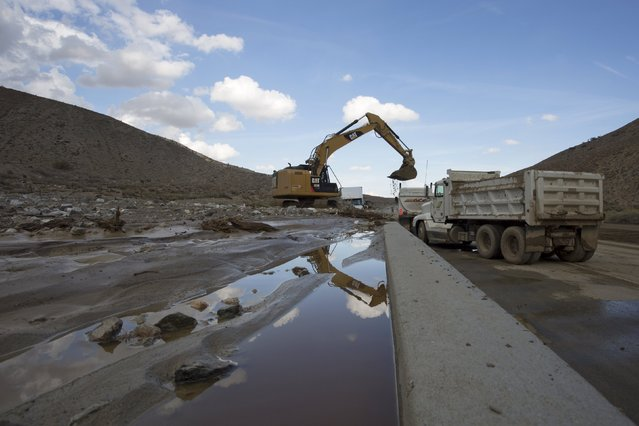 Workers dig out cars and trucks mired in mud and debris on State Route 58 near Tehachapi, California, about 60 miles (97 km) outside of Los Angeles October 17, 2015. (Photo by David McNew/Reuters)
