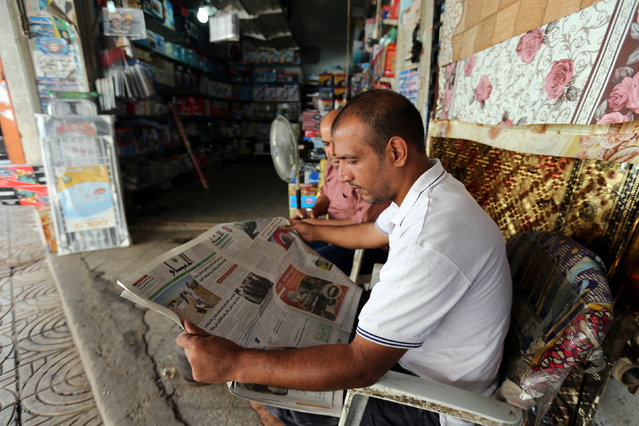 A Palestinian man reads a newspaper outside his store in Gaza City September 19, 2016. (Photo by Ibraheem Abu Mustafa/Reuters)