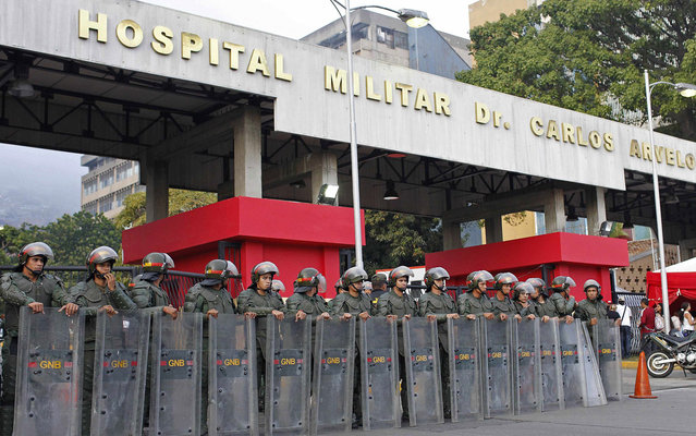 Guards behave outside the hospital in Caracas, Venezuela, where Hugo Chavez, president of the country, was hospitalized when he died. (Photo by Carlos Garcia Rawlins/Reuters)