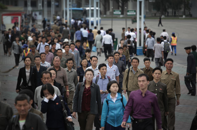 North Korean men and women walk towards a subway station during morning rush hour on Wednesday, September 28, 2016, in Pyongyang, North Korea. Rush hour generally hits its peak at about seven in the morning. Pedestrians hustle along the sidewalks or peddle along on the city's bike lanes, usually narrow strips of sidewalk painted green that started to appear about a year ago, while workers and students who can't walk or bike to where they need to go load onto the subways and fill the city's buses and electric streetcars. (Photo by Wong Maye-E/AP Photo)