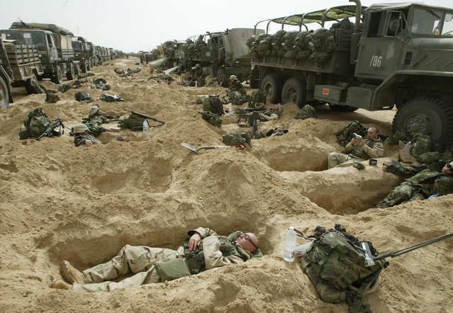 Soldiers from the 3rd Brigade of the U.S. 101st Airborne Division rest in foxholes by their convoy in a staging area in the Kuwaiti desert, on, March 21, 2003. (Photo by Jean-Marc Bouju/AP Photo/The Atlantic)