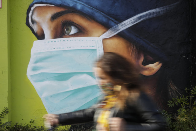 A woman walks in from of a mural painting of a nurse, in Milan, Italy, Wednesday, October 14, 2020. Coronavirus infections are surging again in the Italian northern region where the pandemic first took hold in Europe, putting pressure again on hospitals and health care workers. (Photo by Luca Bruno/AP Photo)