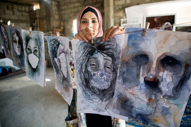 Palestinian artist Khulud al-Desouki hangs her paintings as she works during lockdown at home in Khan Yunis in the southern Gaza Strip, on October 12, 2020, amid strict restrictions due to the COVID-19 pandemic. (Photo by Mohammed Abed/AFP Photo)