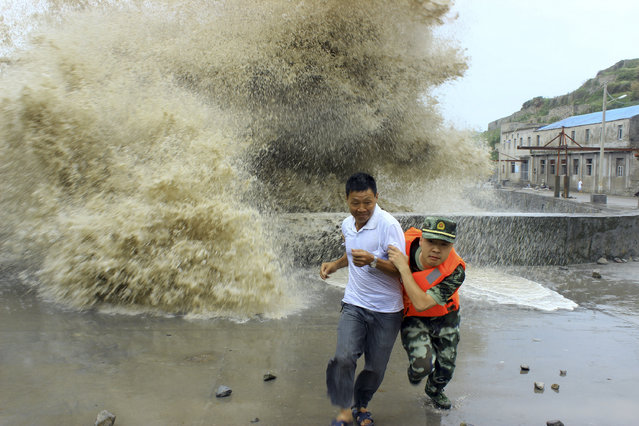 A frontier soldier helps a man move away from waves ahead of Typhoon Soulik in Wenzhou, Zhejiang province, July 13, 2013. (Photo by Reuters/China Daily)