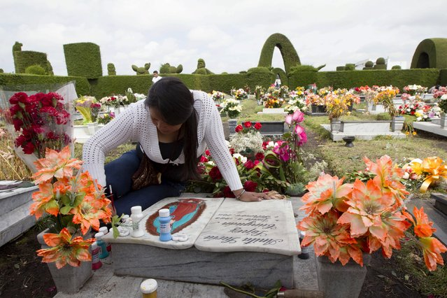 Stephany Lopez, 23, cleans her grandmother's grave at a cemetery known for its topiary art, during the observance of the Day of the Dead, in Tulcan, Ecuador November 2, 2015. (Photo by Guillermo Granja/Reuters)