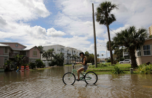 A woman rides her bicycle through flooded streets after Hurricane Matthew hit, near Jacksonville Beach, Florida, U.S., October 8, 2016. (Photo by Henry Romero/Reuters)
