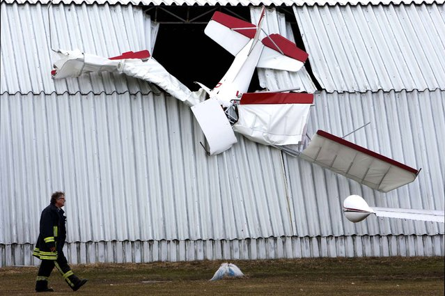A firefighter passes a hangar where a light plane crashed into the roof, killing the pilot, in Neustadt-Glewe, Germany, on April 8, 2013. (Photo by Jens Buettner/Dpa)