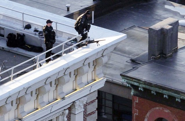 Police are seen on the roof of a building overlooking Boylston Street where explosions went off at the 117th Boston Marathon in Boston, Massachusetts April 15, 2013. (Photo by Jessica Rinaldi/Reuters)