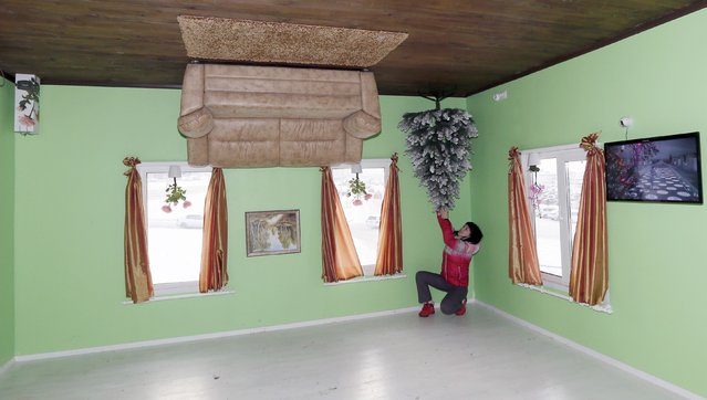 A visitor poses for a picture in a room of a house built upside-down in Russia's Siberian city of Krasnoyarsk, December 14, 2014. (Photo by Ilya Naymushin/Reuters)