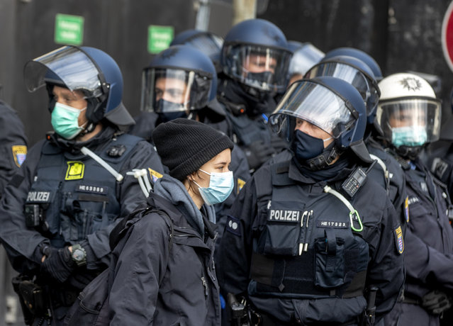 A woman passes police officers during a demonstration of hundreds of people against the government's Corona restrictions in Frankfurt, Germany, Saturday, November 14, 2020. (Photo by Michael Probst/AP Photo)