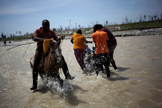 A man crosses a river while riding on a horse after Hurricane Matthew in Les Anglais, Haiti, October 10, 2016. (Photo by Andres Martinez Casares/Reuters)