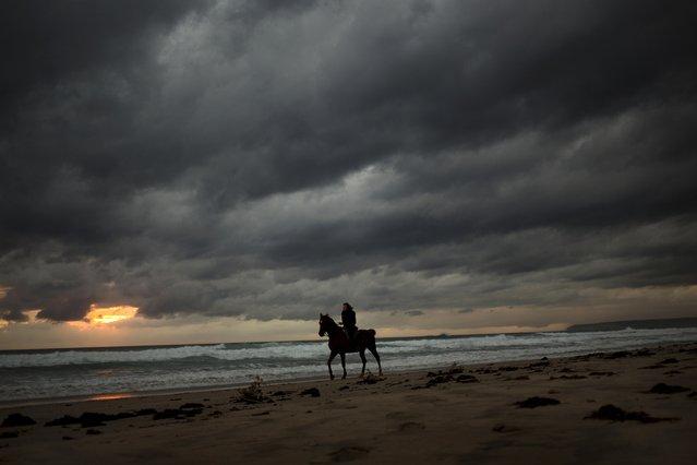 A woman rides a horse along a beach in Cadiz, southern Spain, Monday, October 19, 2015. (Photo by Emilio Morenatti/AP Photo)