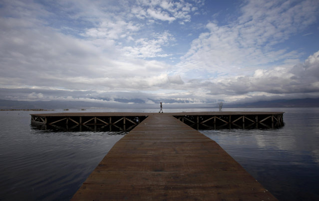 A boy walks on a deck, set in Dojran Lake, in southeastern Macedonia, Sunday, December 7, 2014. (Photo by Boris Grdanoski/AP Photo)