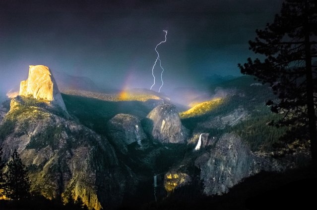 This is the spectacular moment the photographer struck gold – by capturing a bolt of lightning cracking through a rainbow in a freak weather display. (Photo by Nolan Nitschke/Caters News)
