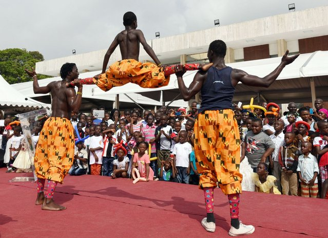 Children watch acrobats as they perform in the garden of the presidential palace in Abidjan, on December 20, 2014 during a Christmas event organised by the Fondation Children of Africa. The event, organised by Ivory Coast's first lady Dominique Ouattarra, president of Fondation Children of Africa, welcomed 3000 children from 16 NGOs and organisations helping children to celebrate Christmas at the presidential palace. (Photo by Sia Kambou/AFP Photo)