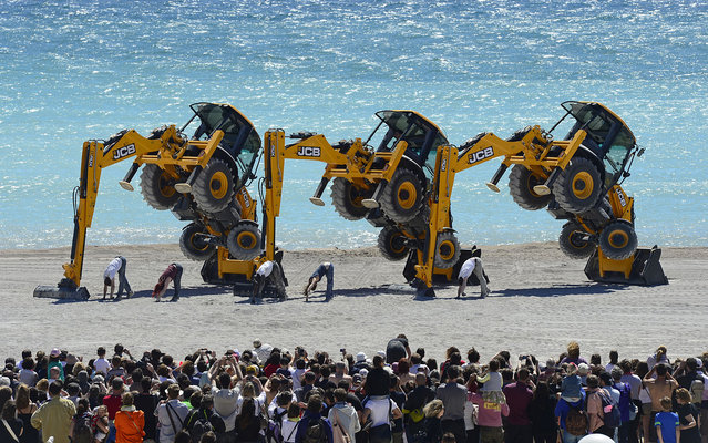 "Dancers from the British theater company Motionhouse perform a show with excavators entitled ""Traction"" on the Prado beach in Marseille, France, on May 10, 2013. (Photo by Boris Horvat/AFP Photo)"