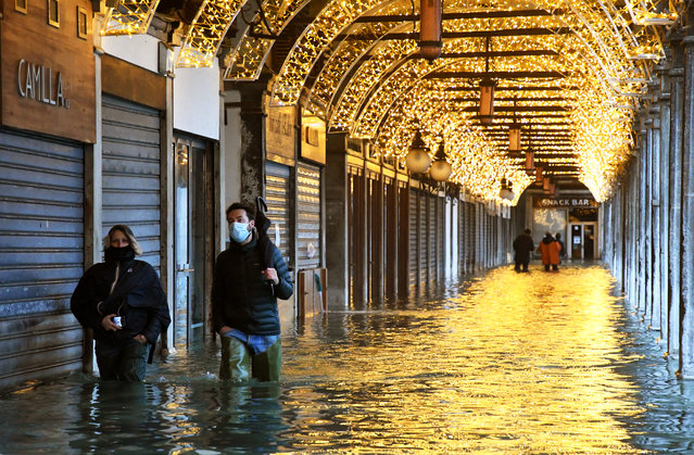 "People walk across an arcade by a flooded St. Mark's Square on December 8, 2020 in Venice following a high tide ""Alta Acqua"" event following heavy rains and strong winds, and the mobile gates of the MOSE Experimental Electromechanical Module that protects the city of Venice from floods, were not lifted (Photo by Andrea Pattaro/AFP Photo)"