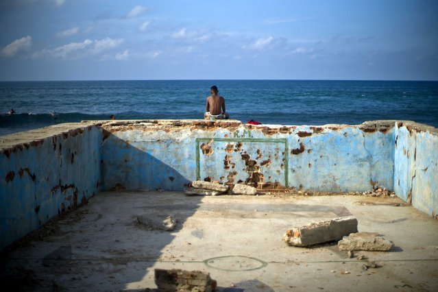 A young man looks at the sea sitting on the wall of an old abandoned pool in Cojimar, Cuba, Wednesday, September 13, 2017. (Photo by Ramon Espinosa/AP Photo)