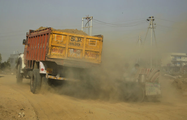 """Smoke emitted from a passing truck and dust engulfs a vendor on the outskirts of New Delhi, India, Saturday, October 22, 2016. A smartphone application that allows citizens to report the presence of construction dust or the burning of leaves and garbage in public parks to authorities was launched Friday in the Indian capital. The """"Hawa Badlo"""", or """"Change the Air"""", app has two versions. One allows citizens to take pictures of likely pollutants. The other allows authorities to investigate and act on valid complaints. (Photo by Altaf Qadri/AP Photo)"""