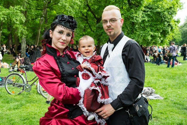 A young family dressed in Victrorian costumes pose for pictures during the traditional park picnic on the first day of the annual Wave-Gotik Treffen, or Wave and Goth Festival, on May 17, 2013 in Leipzig, Germany. The four-day festival, in which elaborate fashion is a must, brings together over 20,000 Wave, Goth and steam punk enthusiasts from all over the world for concerts, readings, films, a Middle Ages market and workshops. (Photo by Marco Prosch)