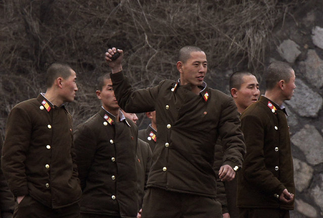 North Korean soldiers practise throwing grenades on the banks of Yalu River in the North Korean town of Sinuiju, opposite the Chinese border city of Dandong, March 6, 2013. (Photo by Jacky Chen/Reuters)