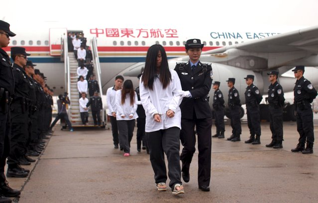 Suspects involved in telecom fraud walk off a plane after being repatriated from overseas, at an airport in Beijing, China, November 10, 2015. Around 254 suspects were escorted back to China on Tuesday from Indonesia and Cambodia, according to local media. (Photo by Reuters/China Daily)