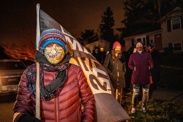 """A woman holds a Black Lives Matter flag as she participates in a call to action """"White People Stop Calling the Cops on Black People"""" protest hosted by Showing Up for Racial Justice Columbus(SURJ) in front of the house of the neighbor who called the police on Andre Hill the night he was shot and killed in Columbus, Ohio on December 28, 2020. - A white police officer who shot dead a Black man in Columbus, Ohio, last week was fired on December 28, city officials said The death of Andre Maurice Hill triggered outrage in a country that has been racked by protests against police brutality and systemic racism since the spring. (Photo by Stephen Zenner/AFP Photo)"""
