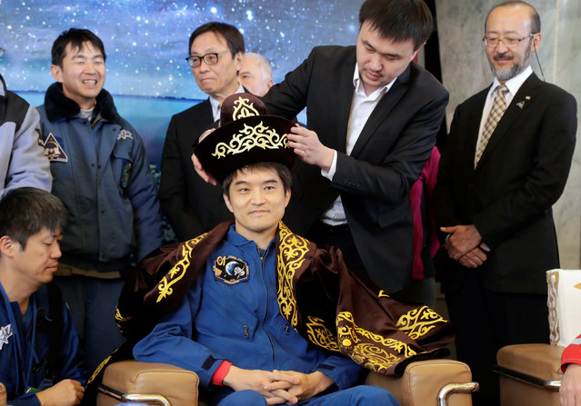 A Karaganda city official presents a Kazakh national costume to International Space Station (ISS) crew member Takuya Onishi of Japan during a news conference at the airport in Karaganda, Kazakhstan, October 30, 2016. (Photo by Dmitri Lovetsky/Reuters)