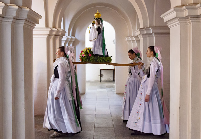 Women dressed in the traditional clothes of the Sorbs carry the statue of Virgin Mary during a procession in the church in Rosenthal, Germany, Monday, May 21, 2018. Traditionally on Whit Monday catholic faithful Sorbs, a Slavic minority near the German-Polish border, celebrate an open air mass in the small village east of Dresden. (Photo by Jens Meyer/AP Photo)