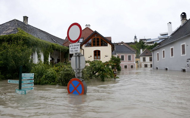 Houses are partially submerged by flood water in the centre of the Austrian village of Emmersdorf, about 100 km (62 miles) west of Vienna June 3, 2013. Torrential rain in Tyrol, Salzburg, Upper and Lower Austria caused heavy flooding over the weekend, forcing people to evacuate their homes. (Photo by Leonhard Foeger/Reuters)