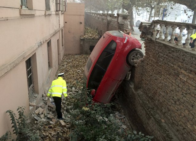 A policeman looks at a car which fell into a pit after crashing through a brick wall, on a hazy day in Xianyang, Shaanxi province, China, November 30, 2015. Local police said the accident occurred in early morning on Monday when the driver could not see the road clearly due to thick fog. No one was injured from the crash, local media reported. (Photo by Reuters/Stringer)