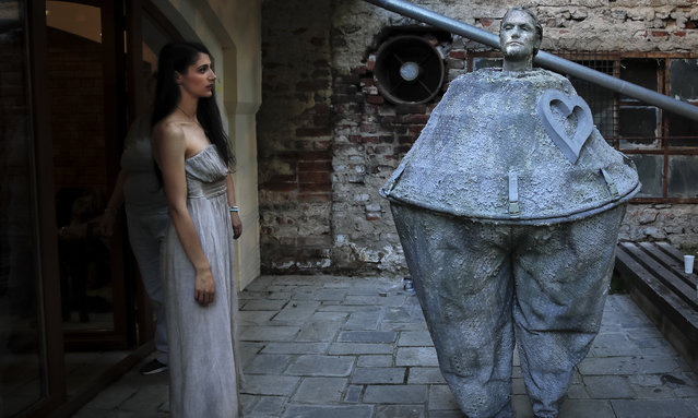 In this Tuesday, May 22, 2018, photograph, a woman looks at an artist of Romania's Masca theatre waiting to perform at the Living Statues International Festival, in Bucharest, Romania. (Photo by Vadim Ghirda/AP Photo)
