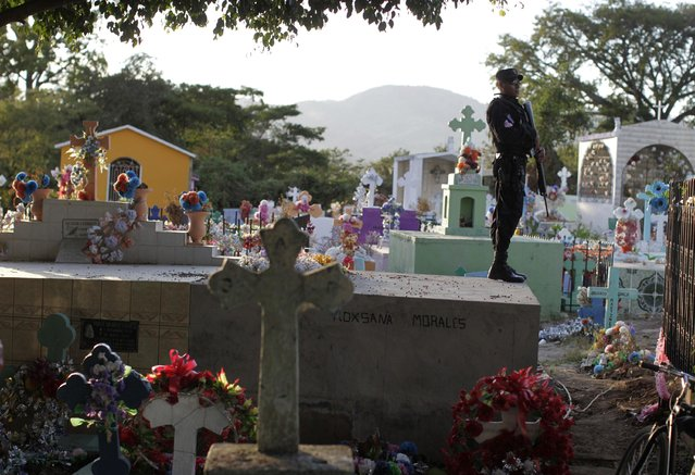 A police officer stands guard at the cemetery during the funeral of a fellow police officer who was killed by alleged gang members in San Juan Opico, January 12, 2015. (Photo by Jose Cabezas/Reuters)