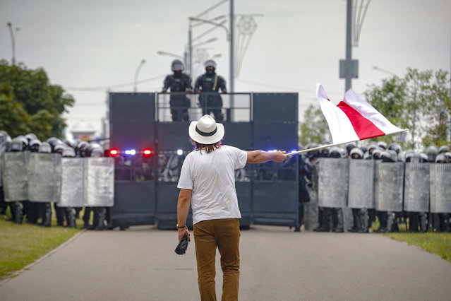 A man waves a historical Belarus flag in front of a riot police blockade during a protest in Minsk, Belarus, Sunday, August 23, 2020. Demonstrators are taking to the streets of the Belarusian capital and other cities, keeping up their push for the resignation of the nation's authoritarian leader, president Alexander Lukashenko, in a massive outburst of dissent that has shaken the country since dubious presidential elections two weeks ago. (Photo by Sergei Grits/AP Photo)