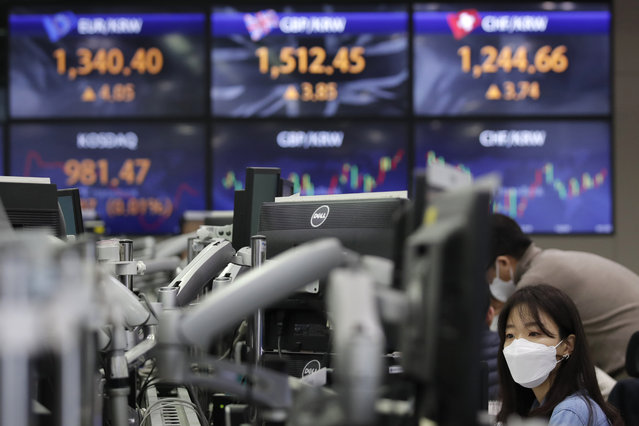 A currency trader watches computer monitors near the screens showing the foreign exchange rates at the foreign exchange dealing room in Seoul, South Korea, Friday, January 22, 2021. Asian stock markets retreated Friday after a resurgence of coronavirus infections in China and a rise in cases in Southeast Asia. (Photo by Lee Jin-man/AP Photo)