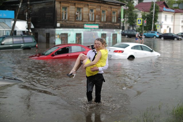 A woman is rescued from her flooded car at the street in Nizhny Novgorod, Russia on June 19, 2018. (Photo by Lucy Nicholson/Reuters)