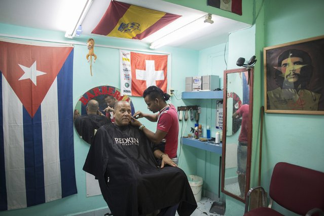 Yoan Viral, 30, (R) cuts the hair of shopowner Acosta, 56, at a barber shop in downtown Havana, January 16, 2015. (Photo by Alexandre Meneghini/Reuters)