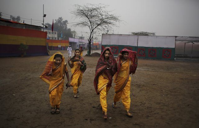 Artists from the Indian state of Maharashtra cover themselves from rain as they walk toward the venue of a media preview displaying a glimpse of culture of different parts of India, in New Delhi, India, Thursday, January 22, 2015. The tableaux will be part of the Indian Republic Day parade on Jan. 26. (Photo by Altaf Qadri/AP Photo)