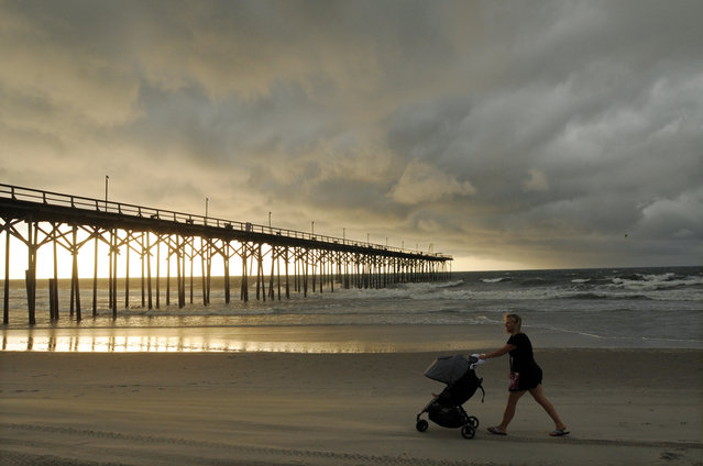 Clouds and rains move in as beachgoers walk along the shore of the north end of Carolina Beach, N.C., Thursday, July 3, 2014. Residents along the coast of North Carolina are bracing for the arrival of the Hurricane Arthur, which threatens to give the state a glancing blow on Independence Day. (Photo by Mike Spencer/AP Photo/Wilmington Star-News)